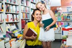 Giovane madre con la figlia nel negozio di libro Fotografie Stock