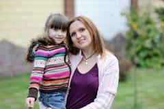 Giovane madre con la sua figlia nel giardino Fotografia Stock Libera da Diritti