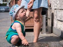 Giovane madre con suo figlio del bambino che gioca all'aperto nella città Immagini Stock