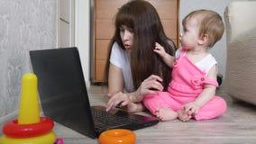Giovane madre con un bambino che lavora ad un computer stock footage