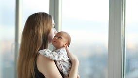 Giovane madre con una figlia neonata che sta vicino alla finestra stock footage