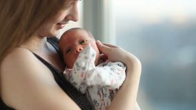 Giovane madre con una figlia neonata che sta vicino alla finestra archivi video
