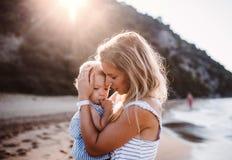 Giovane madre con una ragazza del bambino sulla spiaggia sulla vacanza estiva al tramonto immagini stock libere da diritti