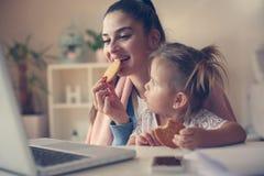 Giovane madre e bambina che mangiano prima colazione e che per mezzo del computer portatile immagini stock