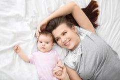 Giovane madre e bambino sveglio sul letto immagini stock