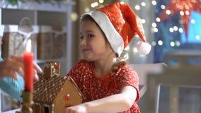 Giovane madre e figlia adorabile nella casa di pan di zenzero rossa della costruzione del cappello insieme video d archivio