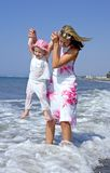 Giovane madre e figlia che giocano nel mare