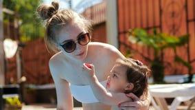Giovane madre e figlia dopo lo stagno che mangiano una prugna stock footage