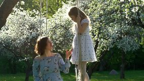 Giovane madre e figlia sveglia nel bello giardino del fiore Movimento lento video d archivio