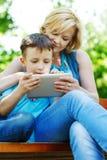 Giovane madre e figlio che giocano sulla compressa Fotografia Stock