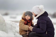 Giovane madre e figlio che si siedono in una neve della Banca della neve in primavera fotografie stock libere da diritti