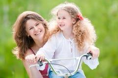 Giovane madre e la sua figlia sulla bicicletta Immagine Stock Libera da Diritti