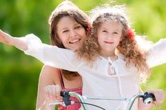 Giovane madre e la sua figlia sulla bicicletta Fotografia Stock