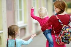 Giovane madre e le sue due figlie sveglie all'aperto immagine stock