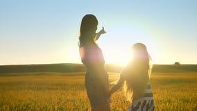 Giovane madre e piccola figlia che camminano nel giacimento di grano, tenentesi per mano ed indicanti le dita in avanti, bello tr video d archivio