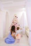 Giovane madre e piccola figlia che decorano l'albero di Natale e p Immagini Stock