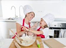 Giovane madre e piccolo derivato dolce in cappello del cuoco e grembiule che cucinano insieme cuocere a casa cucina Fotografie Stock Libere da Diritti