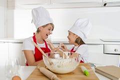 Giovane madre e piccolo derivato dolce in cappello del cuoco e grembiule che cucinano insieme cuocere a casa cucina Fotografia Stock