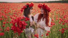 Giovane madre e piccolo supporto della figlia nel campo di fioritura in corone dei fiori selvaggi del papavero archivi video