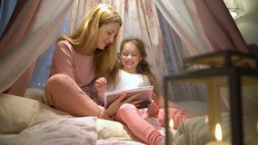 Giovane madre e sua figlia divertendosi facendo uso della compressa che gioca i apps video d archivio