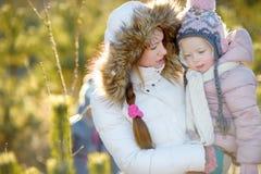 Giovane madre e sua figlia sull'inverno immagine stock