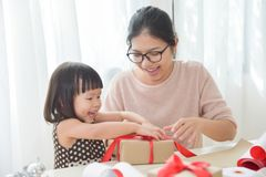 Giovane madre e sua la figlia che avvolgono un contenitore di regalo Fotografia Stock