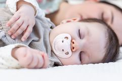 Giovane madre e sua la neonata che dormono nel letto Fotografia Stock Libera da Diritti