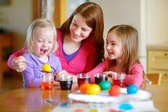 Giovane madre e sue due le figlie che dipingono le uova di Pasqua Fotografia Stock