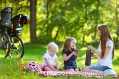 Giovane madre e sue le figlie che hanno un picnic immagini stock