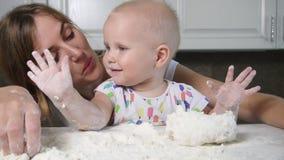 Giovane madre e suo il bambino che preparano pasta sulla tavola Piccolo bambino che gioca con la farina Il panettiere prepara la  video d archivio