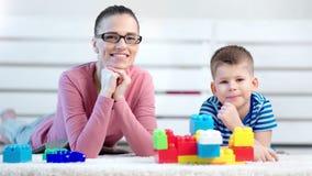 Giovane madre europea affascinante che posa con poco figlio sveglio che sorride e che esamina macchina fotografica archivi video