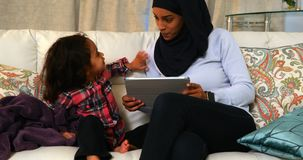 Giovane madre facendo uso di una compressa digitale con sua figlia sul sof? a casa 4k archivi video