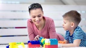 Giovane madre felice adorabile che gioca costruendo gioco con poco figlio sveglio che gode del fine settimana a casa video d archivio