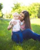 Giovane madre felice che cammina con il suo bambino sveglio al giorno soleggiato di estate Immagine Stock