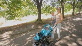 Giovane madre felice che cammina con suo figlio del bambino sul bello vicolo al parco archivi video