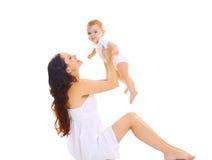 Giovane madre felice che gioca con il bambino su fondo bianco Immagini Stock