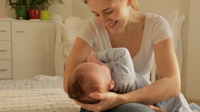 Giovane madre felice che oscilla i suoi 3 mesi del neonato sul letto alla camera da letto archivi video