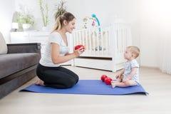 Giovane madre felice che si siede con il suo neonato sulla stuoia di forma fisica e che tiene le teste di legno Fotografia Stock