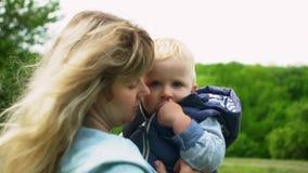 Giovane madre felice che tiene e che bacia suo figlio di un anno nel movimento lento del parco archivi video