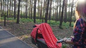 Giovane madre felice con il bambino in carrozzino che cammina nel parco archivi video