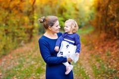 Giovane madre felice divertendosi la figlia sveglia del bambino, ritratto della famiglia insieme Donna con la bella neonata in na fotografia stock libera da diritti