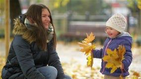Giovane madre felice e la sua piccola figlia divertendosi in Autumn Park, in una mamma e nelle foglie di lancio ed in una risata  video d archivio