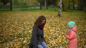 Giovane madre felice e la sua piccola figlia divertendosi in Autumn Park, in una mamma e nelle foglie di lancio ed in una risata  stock footage