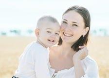 Giovane madre graziosa felice della famiglia che tiene il piccolo figlio del bambino e che sorride nel giacimento dorato della se fotografie stock