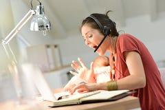 Giovane madre occupata che lavora al computer portatile con il bambino sul suo rivestimento Immagini Stock Libere da Diritti
