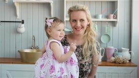 Giovane madre positiva che tiene il suo bambino nella cucina a casa archivi video