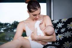 Giovane madre preoccupantesi che allatta al seno il suo poco bambino sul fondo grigio della casa fotografie stock libere da diritti
