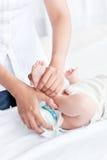 Giovane madre preoccupantesi che cambia il pannolino Fotografie Stock Libere da Diritti