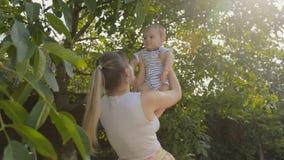 Giovane madre sorridente che solleva suo figlio del bambino sotto l'albero al parco stock footage