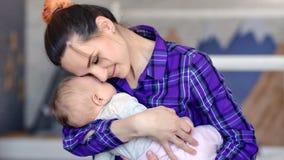 Giovane madre sorridente dei pantaloni a vita bassa che abbraccia il suo piccolo bambino addormentato che tiene a mano primo pian archivi video